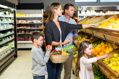 Cute family choosing groceries together Stock Photos
