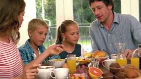 Cute family having breakfast. In the kitchen stock video footage