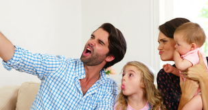 Cute family laughing and taking a photo stock video