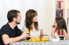 Cute family with little girl eating breakfast Stock Photos