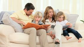 Cute family looking at some albums in the living room Royalty Free Stock Image