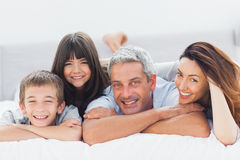 Cute family lying on bed and smiling at camera. At home Royalty Free Stock Photo