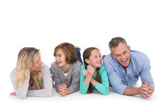 Cute family lying on the floor smiling at camera stock image