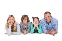 Cute family lying on the floor smiling at camera Stock Images