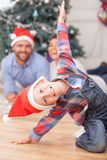 Cute family is making fun near Christmas fir-tree. Cheerful small boy is sitting on flooring and posing near New Year tree. He is wearing red hat. His parents Stock Photography