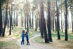 A cute family - mom, dad and son spend fun time outdoors in a beautiful pine forest.  royalty free stock photos