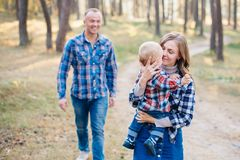 A cute family - mom, dad and son spend fun time outdoors in a beautiful pine forest.  stock photo