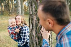 A cute family - mom, dad and son spend fun time outdoors in a beautiful pine forest.  stock photos