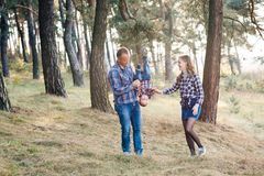 A cute family - mom, dad and son spend fun time outdoors in a beautiful pine forest.  stock photography