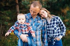 A cute family - mom, dad and son spend fun time outdoors in a beautiful pine forest.  stock image
