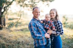 A cute family - mom, dad and son spend fun time outdoors in a beautiful pine forest.  royalty free stock image