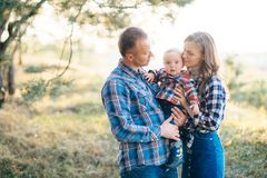 A cute family - mom, dad and son spend fun time outdoors in a beautiful pine forest.  royalty free stock photography