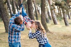 A cute family - mom, dad and son spend fun time outdoors in a beautiful pine forest.  stock images