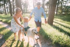 A cute family - mom, dad and son spend fun time outdoors with their dog.  royalty free stock image