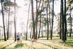 A cute family - mom, dad and son spend fun time outdoors with their dog.  stock images