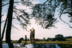 A cute family - mom, dad and son spend fun time outdoors with their dog.  stock photography