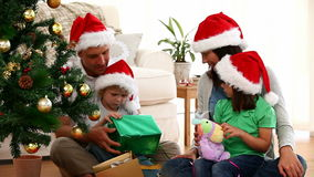Cute family opening Christmas gift sitting on the floor