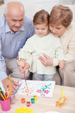 Cute family is painting together at home Royalty Free Stock Photos