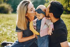 Family spend time in a park. Cute family in a park. Beautyful mother with her little daughter. Man in a black t-shirt royalty free stock photography
