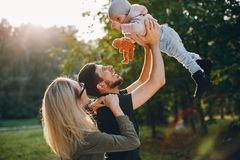 Family spend time in a park. Cute family in a park. Beautyful mother with her little daughter. Woman in a glasses royalty free stock photography