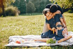 Family spend time in a park. Cute family in a park. Beautyful mother with her little daughter. Woman in a glasses. Picnic in a garden stock photos