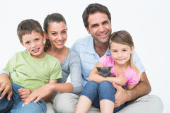 Cute family with pet kitten posing and smiling at camera together Stock Photos