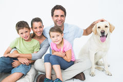 Cute family with pet labrador posing and smiling at camera together Royalty Free Stock Image