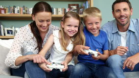 Cute family playing to video games. Sitting on the couch at home stock footage