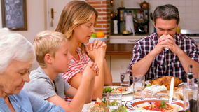 Cute family praying before eating dinner stock footage