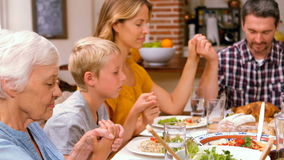 Cute family praying before eating dinner stock video footage