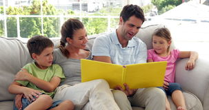Cute family relaxing together on the couch looking at photo album