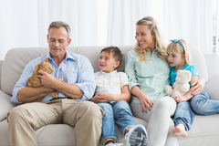 Cute family relaxing together on the couch with their cat Royalty Free Stock Photo