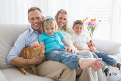 Cute family relaxing together on the couch with their cat Stock Photo