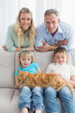 Cute family relaxing together on the couch with their cat Stock Photos