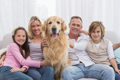 Cute family relaxing together on the couch with their dog. At home in the living room Stock Image