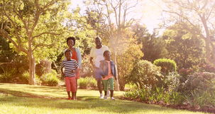Cute family is running in a park. On a sunny day stock footage