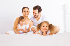 Cute family sitting on the bed in white pajamas Royalty Free Stock Photo