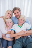 Cute family sitting on couch royalty free stock photography