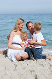 Cute family sitting on the sand Stock Photos