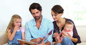 Cute family sitting on a sofa and looking a book together stock video