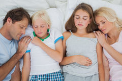 Cute family sleeping together. Cute family sleeping in bed together Royalty Free Stock Image