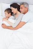 Cute family sleeping together in bed Stock Photo