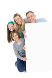 Cute family smiling at camera holding poster. On white background royalty free stock photos
