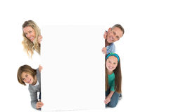 Cute family smiling at camera holding poster Royalty Free Stock Photo