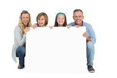 Cute family smiling at camera holding poster stock photography