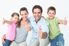 Cute family smiling at camera together showing thumbs up Royalty Free Stock Image