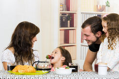 Cute family with two girls eating breakfast Stock Image