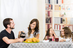 Cute family with two girls eating breakfast Stock Photography