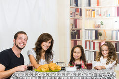 Cute family with two girls eating breakfast Royalty Free Stock Photography