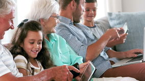 Cute family using electronic devices on the couch. In slow motion stock footage